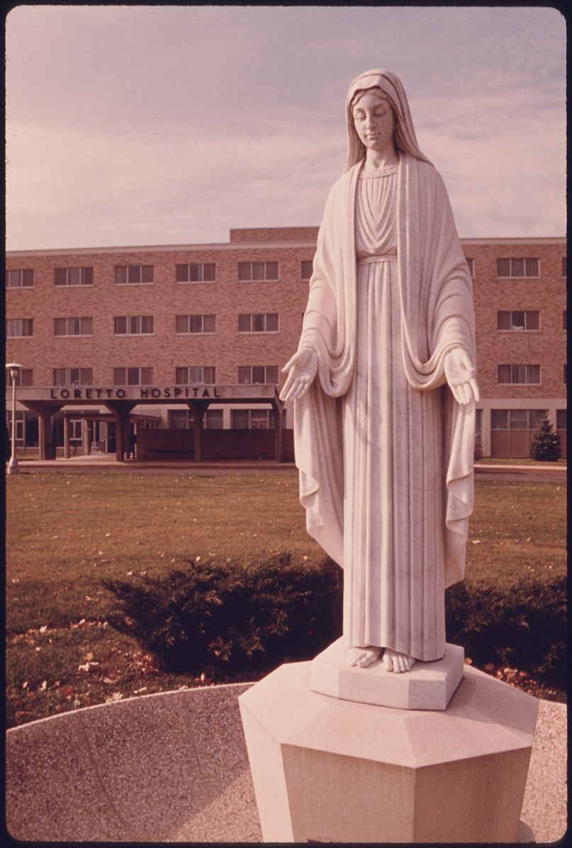 807px-STATUE_OF_THE_VIRGIN_MAY_IN_FRONT_OF_THE_CATHOLIC_LORETTO_HOSPITAL_IN_NEW_ULM,_MINNESOTA._THE_TOWN_WAS_FOUNDED_BY_A..._-_NARA_-_558164